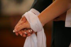 Verklemmte Hände während der orthodoxen kirchlichen Hochzeit stockfotografie