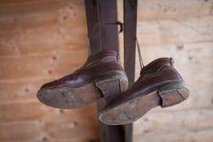 Verklemmte Schuhe, die an Holzbalken hängen Stockbilder