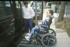 Verklemmter junger Mann des Rollstuhls, der in besonders ausgerüsteten Packwagen kommt stockbild