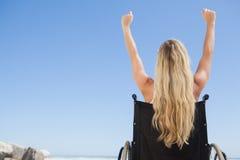Verklemmtes blondes Sitzen des Rollstuhls auf dem Strand mit den Armen oben Stockbilder