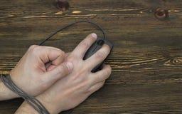 Verklemmtes Handgelenk durch Computermäusekabel Stockfoto