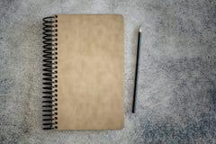 Verklemmtes Notizbuch der gewundenen hellbraunen Abdeckung mit Bleistift auf grauem Hintergrund Stockbilder