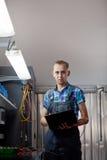 Verklig arbetare för auto mekaniker i garage Automatiskservice och diagnostik arkivfoto