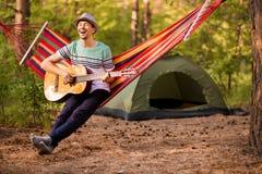 Verklig avkoppling Stilig ung man i hattlekgitarr, medan ligga i hängmatta arkivbilder