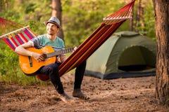 Verklig avkoppling Stilig ung man i hattlekgitarr, medan ligga i hängmatta arkivbild