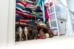 Verklig lägenhetgarderob som organiseras och fylls med kvinnas kläder som visar shopping, livsstilvanor, verkliga livet och att b arkivbilder