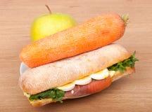 Verklig smörgås med den rökt laxen, ägg och gräsplan med äpplet och moroten på en träbakgrund. Arkivfoton
