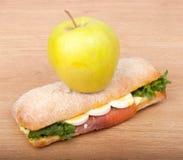 Verklig smörgås med den rökt laxen, ägg och gräsplan med äpplet på en träbakgrund. Royaltyfri Bild