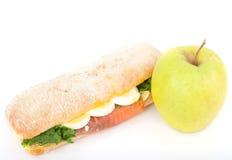 Verklig smörgås med den rökte laxen, ägg och det gröna äpplet på en vitbakgrund. Royaltyfri Bild