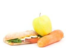 Verklig smörgås med den rökte laxen, ägg och grönt äpple och morot på en vitbakgrund. Arkivbild