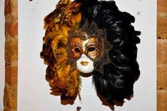 Verklig Venetian maskering på en tegelstenvägg i konstnärligt Murano exponeringsglas gal. arkivfoton