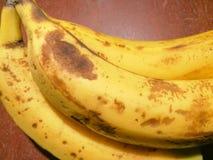 Verkliga bananer överst av en brun tabell Arkivbilder