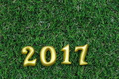 2017 verkliga 3d objekt på grönt gräs, begrepp för lyckligt nytt år Arkivfoto