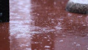Verkliga regndroppar som glider på golvet av en terrass lager videofilmer