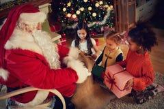 Verkliga Santa Claus ger gåvor till ungar Arkivbilder