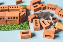 Verkliga små lerategelstenar på tabellen tidigt lära Framkallande leksaker guld för begreppskonstruktionsfingrar houses tangenter Arkivfoton