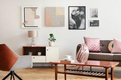 Verkligt foto av den vita vardagsruminre med affischen på väggen, soffan med kuddar och filten, träkaffetabell med boken och arkivfoto
