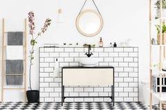 Verkligt foto av en badruminre med ett skåp, tegelplattor, spegeln, blomman och stegen med handdukar royaltyfria bilder