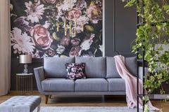 Verkligt foto av en blom- vardagsruminre med en tapet, en soffa och växter royaltyfri fotografi
