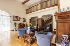 Verkligt foto av en elegant vardagsruminre med den blåa soffan och fåtöljer, trätrappa, vaktstång och tabell royaltyfri bild