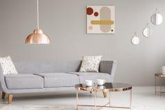 Verkligt foto av en enkel soffa, en kopparlampa och tabell och en målning på en vägg i en vardagsruminre fotografering för bildbyråer