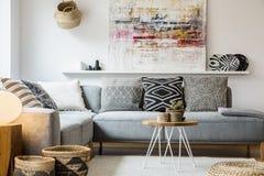 Verkligt foto av en hemtrevlig soffa med kuddar som står bak ett litet royaltyfri foto