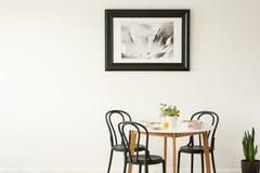 Verkligt foto av en lagd äta middag tabell med svartstolar och att måla på en tom vägg Förlägga ditt diagram royaltyfri fotografi