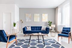 Verkligt foto av en modern vardagsruminre med en soffa, armchai arkivfoton