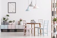 Verkligt foto av en pastellfärgad matsalinre med en tabell, stolar royaltyfri fotografi