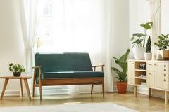 Verkligt foto av en retro soffa bredvid wi för en kaffetabell och kabinett arkivbilder