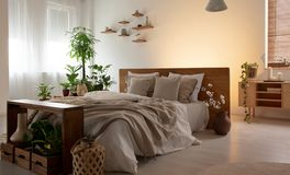 Verkligt foto av en romantisk sovruminre med en dubbelsäng med ark, växter och trähyllor royaltyfria bilder