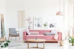 Verkligt foto av en rosa soffa med kuddar som står bak en tabell, royaltyfri foto