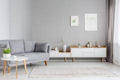 Verkligt foto av en rymlig vardagsruminre med grå soffasta arkivfoto