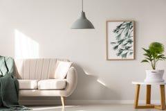 Verkligt foto av en soffa med filt- och kuddeanseende bredvid a arkivfoto