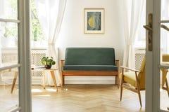 Verkligt foto av en tappningvardagsruminre med en grön soffa, royaltyfri fotografi