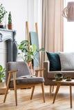 Verkligt foto av ett stolanseende bredvid en kaffetabell och en soffa royaltyfri foto