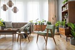 Verkligt foto av ett stolanseende bredvid tabeller och en soffa i ett r royaltyfri foto