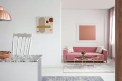 Verkligt foto av målningar i en rymlig vardagsruminre med en rosa soffa- och kopparkaffetabell royaltyfri foto