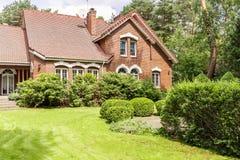 Verkligt foto av trädgården med buskar och det härliga tegelstenhuset arkivbild