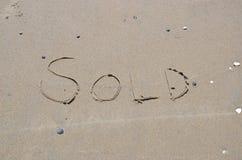 Verkocht geschreven in het zand op het strand Stock Fotografie