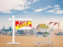 Verkocht huisteken met spot op huis in boodschappenwagentje Stock Foto