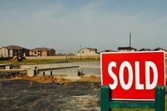 Verkocht Teken met nieuwe huizen op de achtergrond Stock Foto