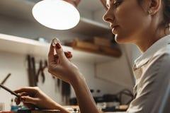 verkollkommnung Schließen Sie oben vom jungen weiblichen Juwelier, der einen Ring schaut und kontrolliert lizenzfreies stockbild