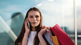 Verkoop, consumentisme: De jonge vrouw met smartphones en het winkelen doet status en het spreken dichtbij winkelend centrum in z stock videobeelden