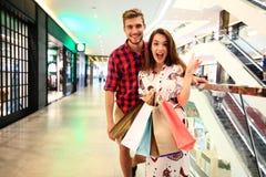 Verkoop, consumentisme en mensenconcept - het gelukkige jonge paar met het winkelen doet het lopen in wandelgalerij in zakken royalty-vrije stock foto