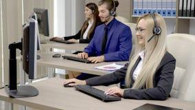 Verkoop die team in het bureau op de markt brengen die op de hoofdtelefoonreeks spreken stock videobeelden