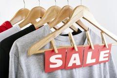 Verkoop in een kledingsopslag - kortingsteken bij een klerenrek stock afbeeldingen