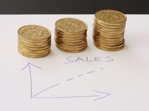 Verkoop en financiële bedrijfsgrafiek - overhandig getrokken met ballpoint op Witboek en stapels van gouden geldmuntstukken die w stock afbeelding