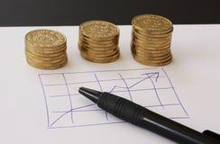 Verkoop en financiële bedrijfsgrafiek - overhandig getrokken met ballpoint op Witboek en stapels van gouden geldmuntstukken die w royalty-vrije stock afbeeldingen