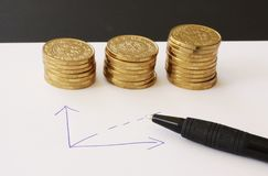 Verkoop en financiële bedrijfsgrafiek - overhandig getrokken met ballpoint op Witboek en stapels van gouden geldmuntstukken die w royalty-vrije stock foto